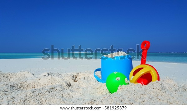 Bucket and spade child toy on the white sand beach with blue aqua sea and sky background