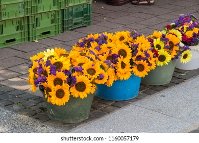 Bucket of sunflowers and matching other flowers at a stall at a farmers market