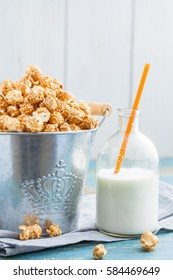 A bucket with a sweet caramel popcorn and a bottle of milk and straws on a worn blue table.