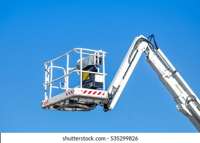 Bucket truck high up of a crane with blue sky