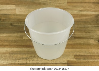 A bucket with water on wooden background