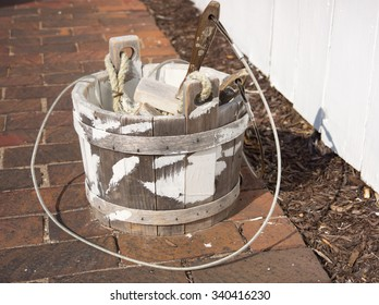 a bucket of whitewash and brush beside a white whitewashed fence