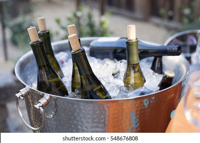 Bucket of wine bottles at a backyard party.