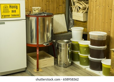 buckets full of extracted honey out of centrifuge and Beekeeper equipment - yellow german sign saying homemade honey