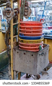 Buckets onboard trawler in Brixham harbour in Devon, UK. Rear of fishing vessel moored up in the harbour. buckets for sorting out fish.