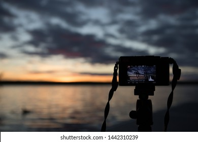 Buckhorn lake, Ontario, Canada,July 1, 2019.  Set up of my point and shoot camera for a timelapse capture. Camera on tripod, and I captured the set up with my DSLR overlooking the sunset image.