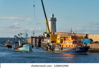 BUCKIE, MORAY, SCOTLAND - 17 OCTOBER 2018: Buckie Lifeboat tows a broken down Fishing Boat into the harbour at Buckie, Moray, Scotland on 17 October 2018