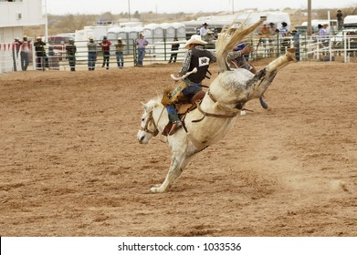 Bucking action during the saddle bronc riding competition at a rodeo.