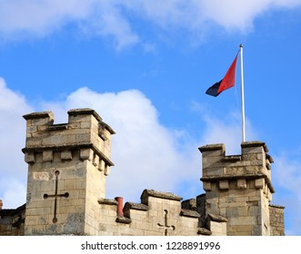 Buckingham, Buckinghamshire, UK 10.11.2018 - Sky view of Buckingham Gaol / Museum turrets with flag flying against a blue and cloudy sky.  Popular tourist attraction.