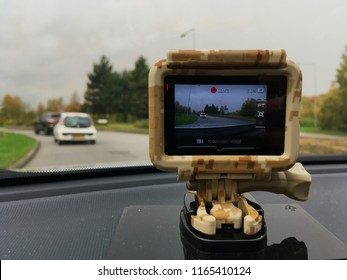 Buckingham, UK - 16 October 2018: Close up of a GoPro hero black dashcam camera in a camo case housing recording footage while driving on the road for accident safety.