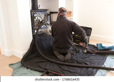 BUCKINGHAM, UK - April 20, 2020. Modern chimney sweep sweeping chimney with a flue liner in a home, UK