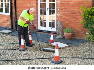 BUCKINGHAM, UK - August 07, 2015. Man jetting sewage drain outside house, drain cleaning company unblocking main sewage pipe, UK