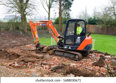 BUCKINGHAM, UK - February 13, 2016. Digger, bulldozer clearing rubble in preparation for hard landscaping a garden in UK