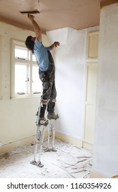 Buckingham, UK - May 07, 2015. A plasterer skims a high ceiling whilst standing on stilts. A skilled plasterer can work far more quickly on stilts compared to using a platform.