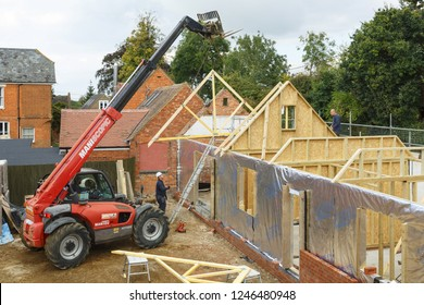 Buckingham, UK - October 13, 2016. Heavy machinery lifts a roof truss into place on an extension to a period house. The extension is of timber frame construction.