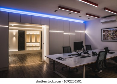 Buckinghamshire, United Kingdom February 2018: Modern office with variable lighting including desk, chairs and computer.