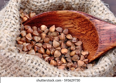 Buckwheat in a bag and spoon on wooden table