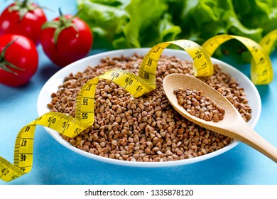 Buckwheat bowl and spoon with fresh ripe vegetables and yellow measuring tape. Buckwheat cereal grains for dietary, healthy eating. Fiber and slimming food. Diet concept