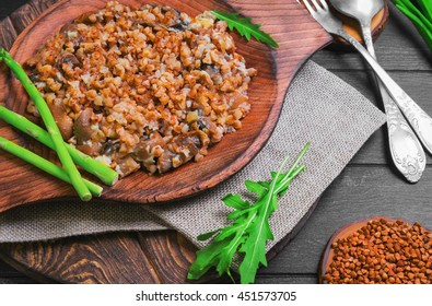 Buckwheat Cereal with roasted Mushrooms in wooden plate, raw buckwheat to cereal, asparagus, silver fork and spoon, green lettuce leaves on dark black background wooden surface