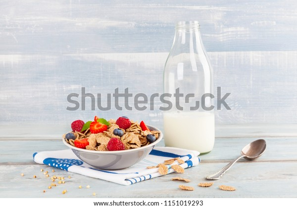 Buckwheat flakes with berries in bowl and jar of milk. Delicious healthy breakfest concept.