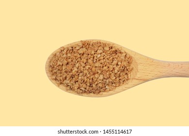 Buckwheat flakes in a big wooden spoon isolated on a  light yellow background, diet product, natural color, high contrast.