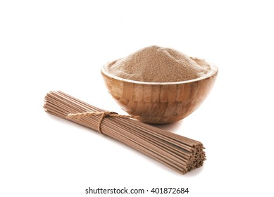 buckwheat flour in bowl and soba noodles isolated on white background