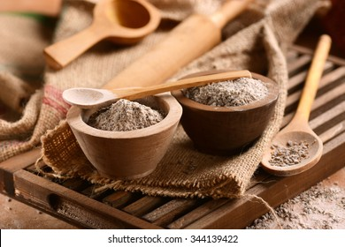 buckwheat flour in the wooden bowl on the table