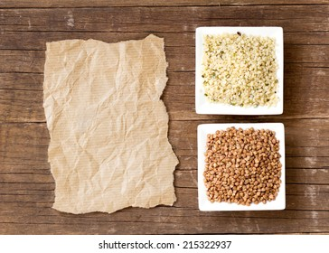 Buckwheat, hemp seeds and paper on wooden table