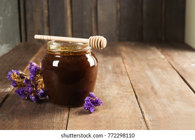Buckwheat honey with flowers over wooden background
