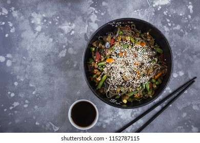 Buckwheat noodles with meat and vegetables, Asian wok on a gray