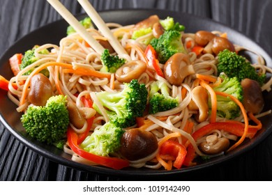 Buckwheat noodles with mushrooms and vegetables close-up on a plate. horizontal
