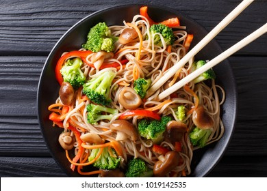 Buckwheat noodles with mushrooms and vegetables close-up on a plate. Horizontal top view from above