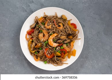 Buckwheat noodles with seafood and vegetables, top view, horizontal