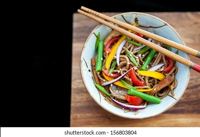 Buckwheat noodles (soba) with chicken and vegetables on the wooden board and black background