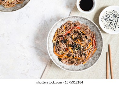 Buckwheat noodles with vegetables and meat decorated with sesame and seaweeds in bowls on grey background. Top view.