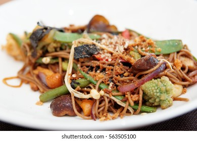 Buckwheat noodles with vegetables and mushrooms on plate, close-up