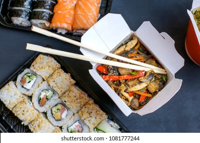 Buckwheat noodles with vegetables in a paper box and rolls with fish on a black background