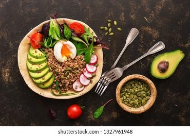 Buckwheat porridge with boiled egg, avocado, radish, chard leaves, arugula, tomatoes and seeds. Buddha bowl with healthy food. Top view
