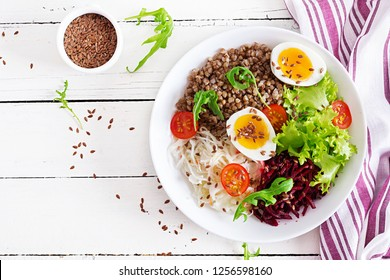 Buckwheat porridge buddha bowls with beetroot, cabbage, boiled eggs and  fresh tomato on white table. Healthy breakfast. Top view