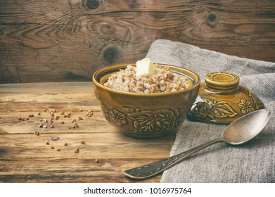 buckwheat porridge with butter in a ceramic pot on old wooden table, Russian cuisine, simple food