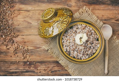 buckwheat porridge with butter in ceramic pot, on old wooden table, Russian cuisine, top view