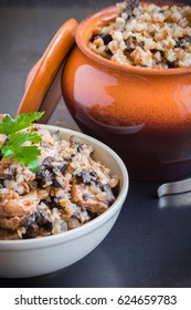 Buckwheat porridge with mushrooms and chicken meat  in a ceramic pot on grey background.