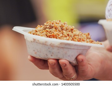 Buckwheat porridge in a plastic plate in the hands of a woman in nature .
