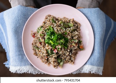 Buckwheat porridge with vegetables, parsley, dill, onion, greens and spices. Russian traditional buckwheat porridge in ceramic pink plate. Holding in hands. Vegan food concept.