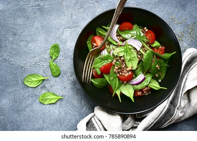 Buckwheat salad with spinach, cherry tomato and red onion in a black bowl over dark grey slate, stone or concrete background.Top view with copy space.