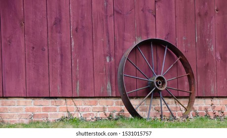 Bucolic scene of antique wheel leaning against red barn. Copy space.