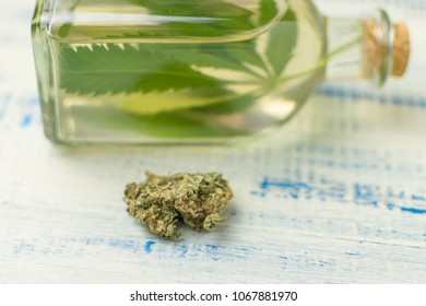 A bud of marijuana against the background of a bottle of marijuana essence.