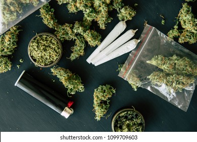 Bud of marijuana flowers on scales, grinder and shredded cannabis joint and a packet of weed and Smartphone on a black wood background