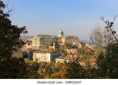 Buda Castle in Budapest, Hungary. View from Gellert Hill. Beautiful landscape with castle in cityscape viewed through greenery of park Citadella.