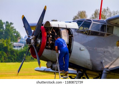 Budaors Hungary Sept 2 2018: Aircraft mechanic carry out some repairs on the engine of airplane An - 2 . as a regular airplane maintenance.